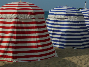 Dicht aneinandergereiht drängen sich die bunt-gestreiften Badezelte am Grande Plage in Biarritz.
