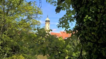 Blick durch das dichte Grün am westlichen Murufer auf den Turm der Franziskanerkirche. © 2017 Reinhard